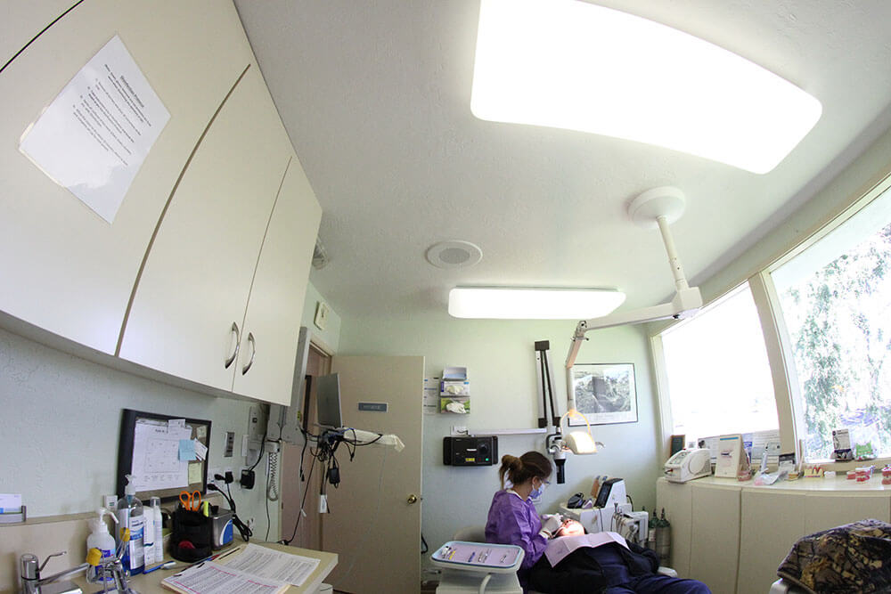 A woman in purple scrubs, goggles, face mask, and gloves works on a patient in a dental chair in a treatment room
