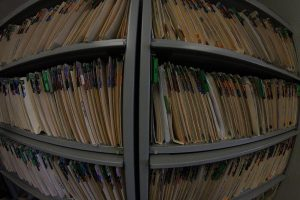 Wide-angle image of shelves of patient files, all with multi-colored tabs