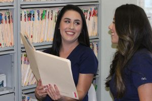 Two women with dark hair and wearing purple scrubs, smiling and looking at a patient's case folder