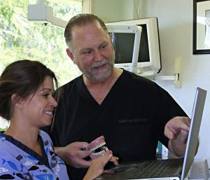 Dr. Cooper holds a model of teeth and points to the screen on a laptop, while a dental assistant observes