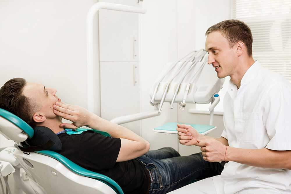 Doctor speaking with a patient who is sitting in the treatment chair holding the side of his face