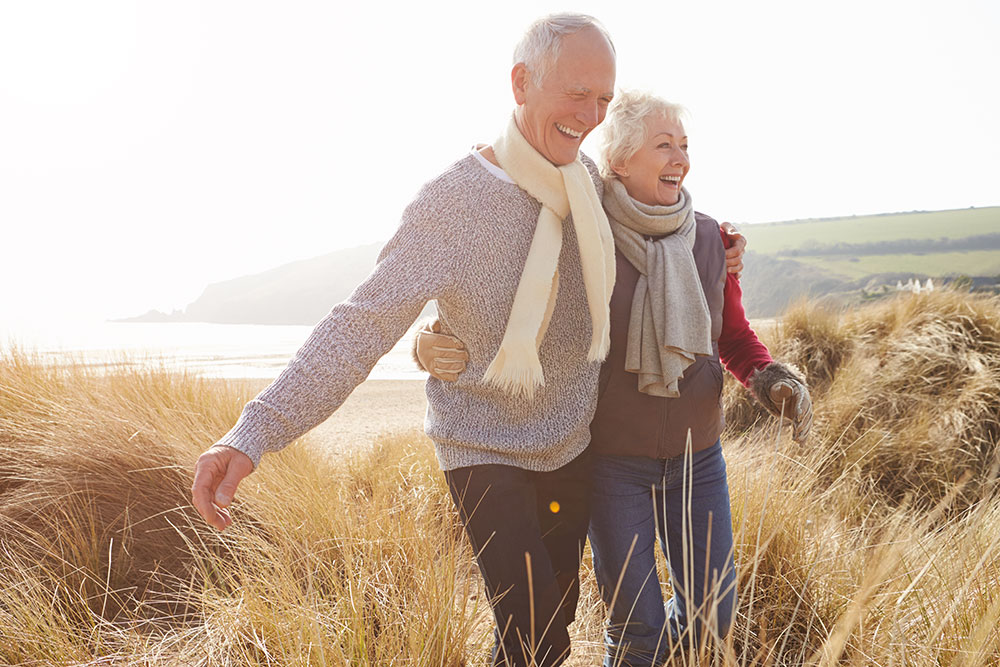 Older couple walking through tall grass with hills and a beach in the background